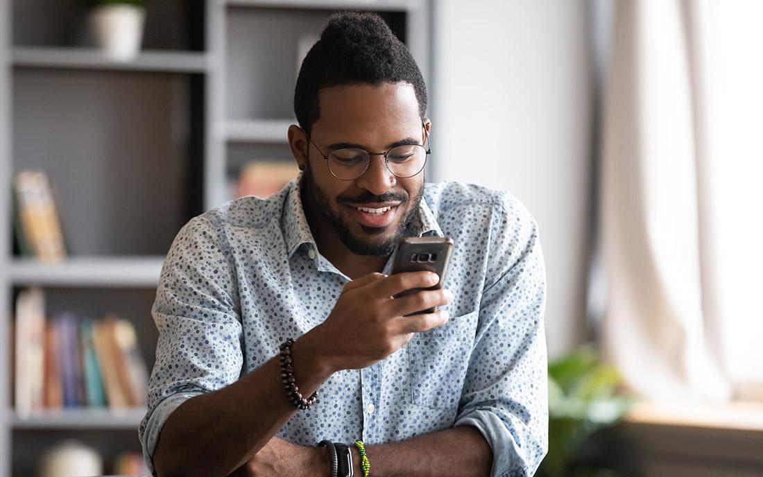 Feliz joven africano hombre de negocios estudiante profesional usuario mantenga smartphone moderno gadget mensaje de texto en la aplicación de redes sociales en línea sentarse en el escritorio de la oficina en casa utilizando tecnología de teléfono celular para navegar por la web